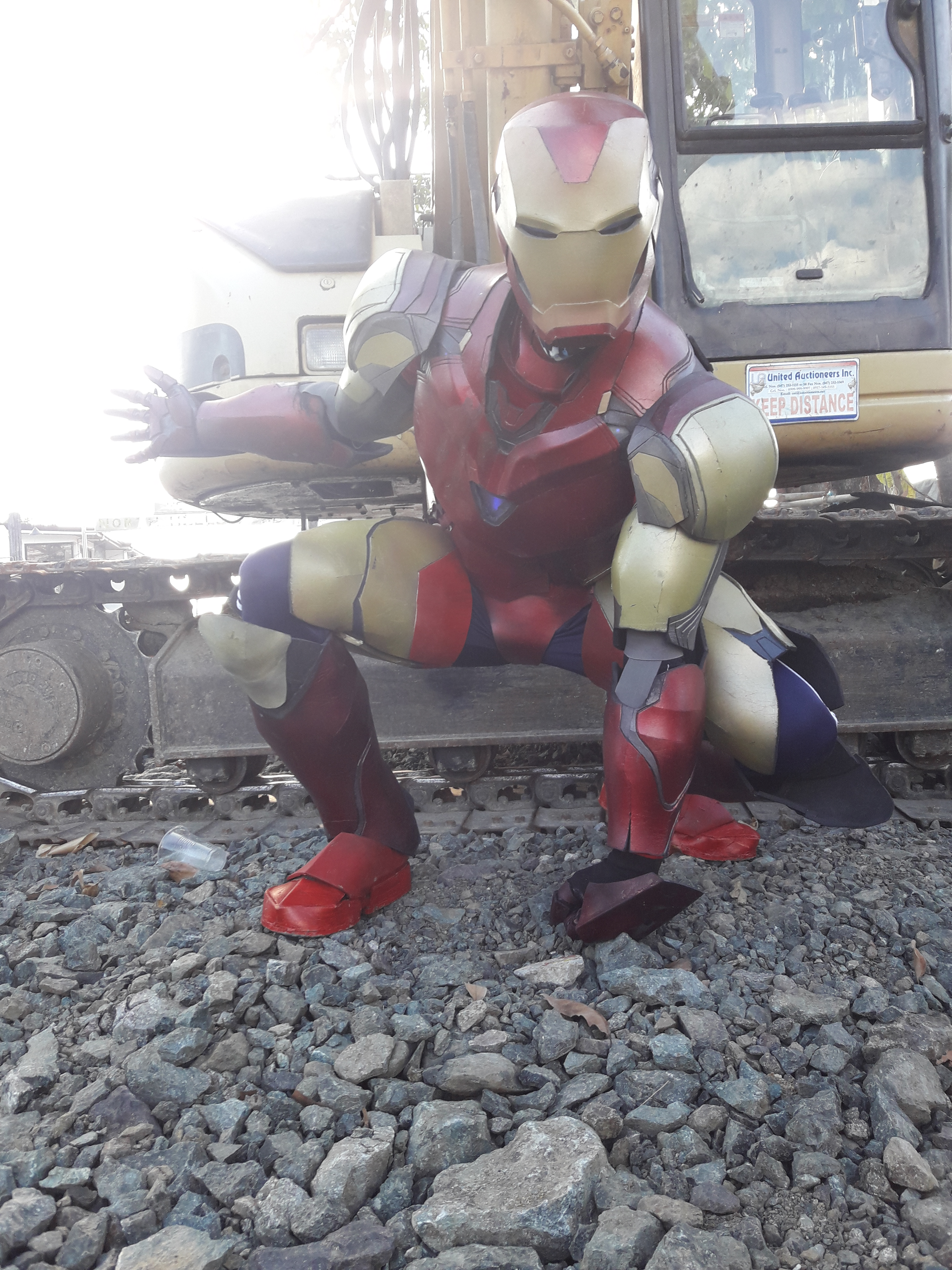 Man in red and yellow Iron Man armor, crouching