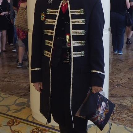Cosplayer in fancy coat and feathery hair