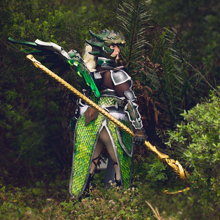 Woman in green scay armor and gold staff