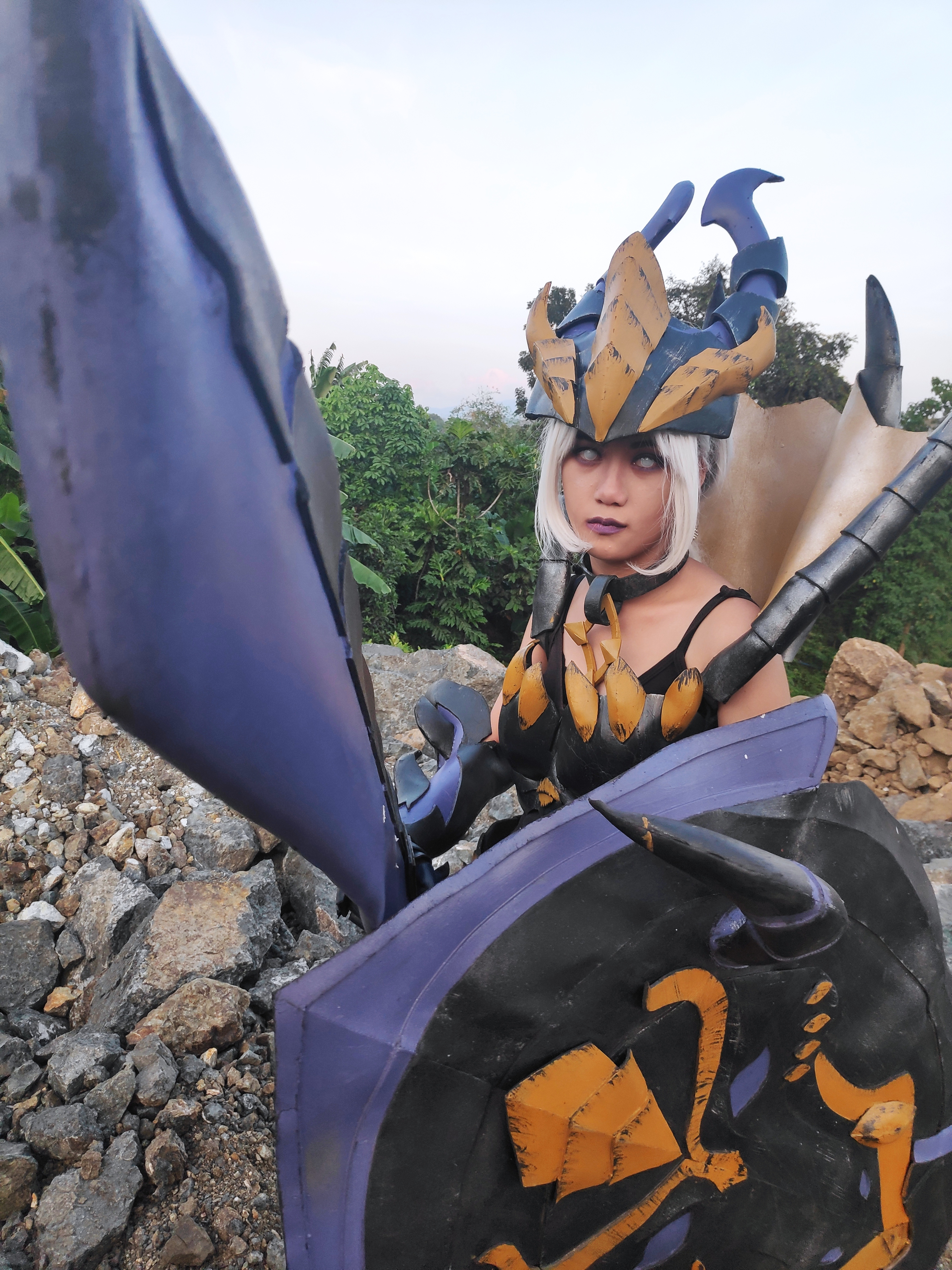 Armored woman pointing sword at camera