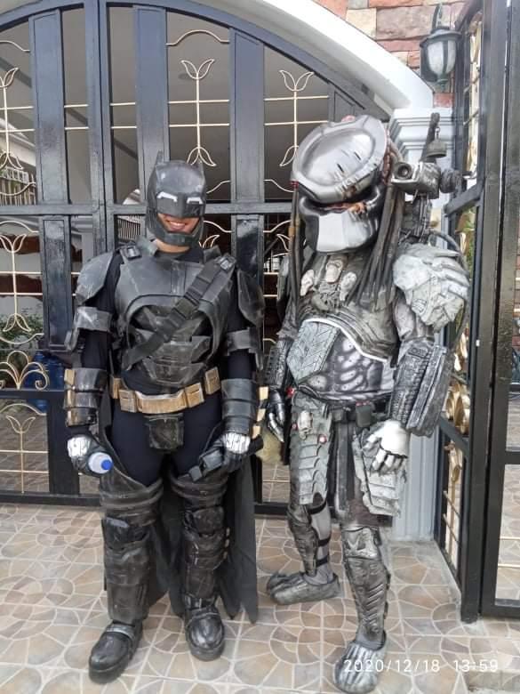 Cosplayers dressed as Batman and Predator (helmet on)