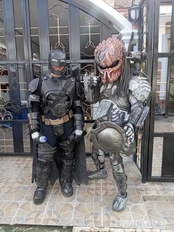 Cosplayers dressed as Batman and Predator (helmet off)